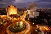 Early evening view of the Hotel Indonesia roundabout, Welcome monument and buildings along Jalan Thamrin, Jakarta - Martin Westlake