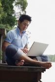 Man sitting on jetty, using laptop - Marcus Mok