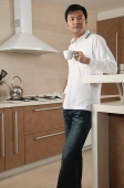Man standing in kitchen, holding cup, looking away - blueduck