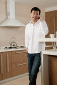 Man standing in kitchen, using mobile phone - blueduck