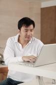 Man sitting at kitchen counter, using laptop - blueduck