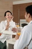 Man and woman sitting in kitchen, having breakfast - blueduck