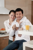 Couple in kitchen, woman with arm around man's shoulder, smiling at camera - blueduck