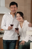 Couple in kitchen, holding wine glasses, looking at camera, portrait - blueduck