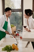 Couple in kitchen, man chopping vegetables, woman leaning on counter with wine glass - blueduck