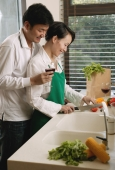 Couple in kitchen, woman chopping vegetables, man standing next to her, holding wine glass - blueduck