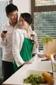 Couple in kitchen holding wine glasses, woman turning to look at man - blueduck