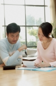 Couple sitting at table, looking at documents - blueduck