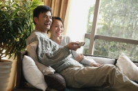 Couple in living room, sitting side by side on sofa, man holding TV remote control - blueduck