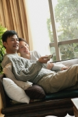 Couple sitting side by side on sofa, man holding TV remote control - blueduck