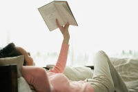 Woman lying on sofa, reading a book - blueduck