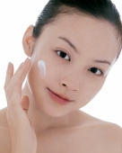Young woman looking at camera, applying moisturizer on face - blueduck