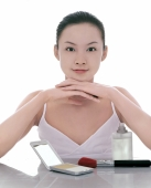 Young woman looking at camera, make-up on the table around her - blueduck