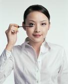 Young woman looking at camera, applying mascara - blueduck