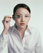 Young woman applying mascara - blueduck