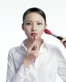 Young woman applying make-up - blueduck