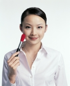 Young woman holding make-up brush to cheek - blueduck