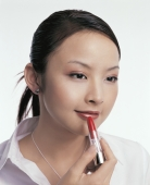 Young woman applying lipstick - blueduck