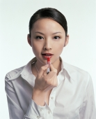Young woman applying lipstick, looking at camera - blueduck