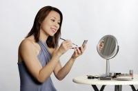 Woman sitting, applying make-up - Yukmin