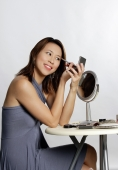 Woman looking at compact mirror, applying eyeshadow - Yukmin