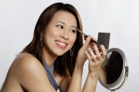 Woman applying eye shadow, looking at compact - Yukmin