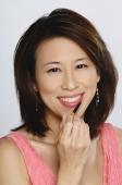 Woman applying lip-liner, smiling at camera - Yukmin
