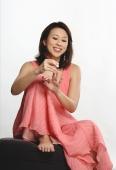 Woman sitting down applying nail polish on fingers - Yukmin
