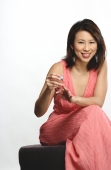 Woman applying nail polish on fingers, smiling at camera - Yukmin