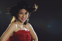 Woman in tube top wearing cowboy hat, smiling at camera - Yukmin