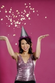 Woman wearing party hat, throwing popcorn in air - Yukmin