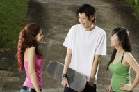 Three teenagers talking, young man holding skateboard - Yukmin