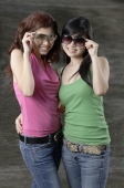 Two teenage girls, standing side by side, adjusting sunglasses - Yukmin