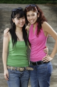 Two teenage girls, standing side by side, smiling at camera - Yukmin
