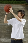 Young man holding basketball, aiming - Yukmin