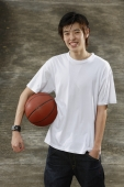 Young man with basketball, hand in pocket - Yukmin