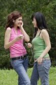 Teenage girls standing outdoors, listening to MP3 player - Yukmin