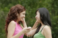 Two teenage girls listening to MP3 player, smiling - Yukmin