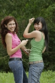 Two teenage girls listening to MP3 player, dancing and smiling at camera - Yukmin
