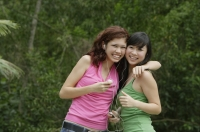 Teenage girls standing side by side, embracing, listening to MP3 player - Yukmin