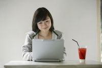 Young woman using laptop, drink on table next to her - Yukmin