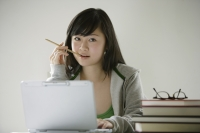 Young woman with laptop, biting pencil, looking at camera - Yukmin