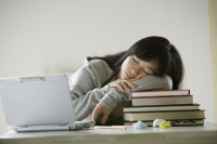 Young woman sleeping on stack of books, laptop open next to her - Yukmin