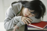 Young woman sleeping on stack of books - Yukmin