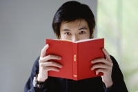Young man with book covering his face, looking at camera - Yukmin