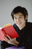 Young man with book smiling at camera - Yukmin