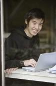Young man using laptop, smiling at camera - Yukmin