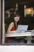 Young woman sitting at table, using laptop, looking through window - Yukmin