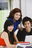 Teenagers with laptop and books, smiling at camera, portrait - Yukmin