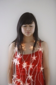 Young woman with eyes closed, wearing fairy lights - Yukmin